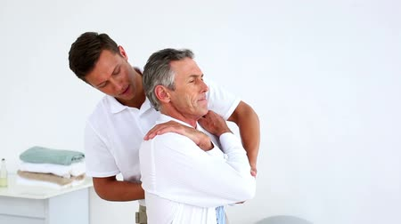 terapeuta : Stressed businessman getting his shoulders aligned by physiotherapist at the rehabilitation center