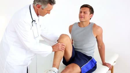 kolano : Mature doctor checking sportsmans injured knee in his office at the hospital