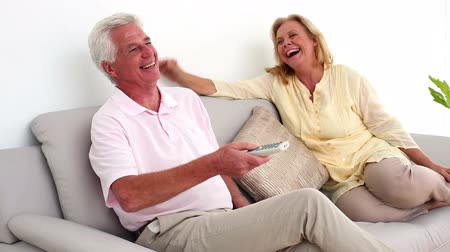 smích : Retired smiling couple watching television on the couch at home in the sitting room
