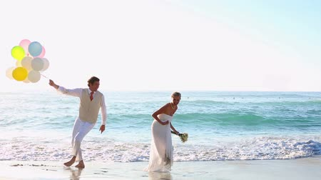 подвенечное платье : Newlyweds laughing and playing with balloons on the beach on their wedding day