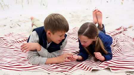 пикник : Siblings lying on blanket on the beach talking on a chilly day