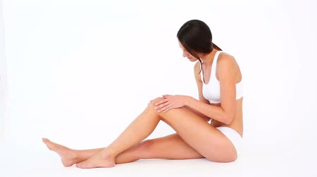 doloroso : Fit woman touching her sore knee and shaking her head on white background Stock Footage