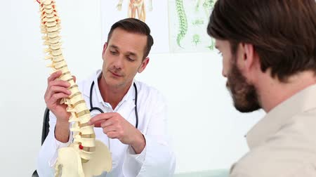 fizjoterapeuta : Doctor showing his patient a spine model in his office at the hospital