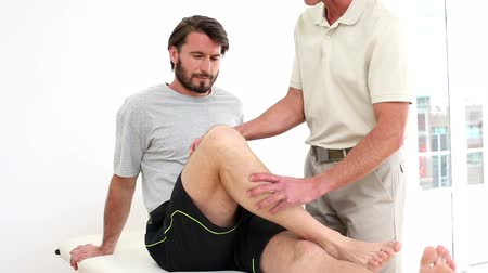 terapeuta : Physical therapist checking injured patients knee in his office at the hospital