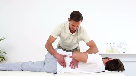 terapeuta : Physical therapist checking patients lower back in his office at the hospital Stock Footage