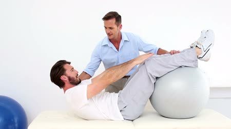 terapeuta : Physical therapist helping his patient do a sit up in his office at the hospital
