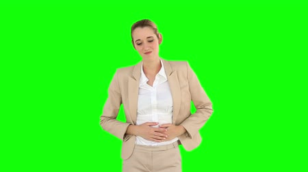 żołądek : Businesswoman rubbing her sore stomach on green screen background