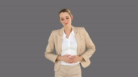 gyomor : Businesswoman rubbing her sore stomach on grey screen background Stock mozgókép
