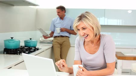 hot news : Woman using laptop while her husband is standing reading the newspaper at home in the kitchen