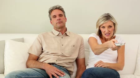 realizing : Woman stealing the remote control from her dozing husband on the couch at home in the living room Stock Footage