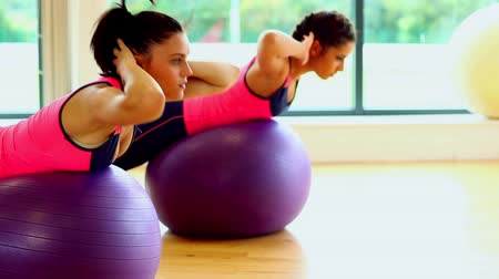 Lovely focused women training their bellies  using fitness balls