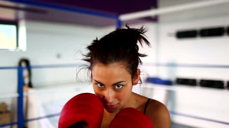 boxe : Aggressive fit woman wearing red boxing gloves boxing looking at camera