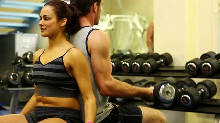 Two fit people lifting dumbbells sitting in gymnasium