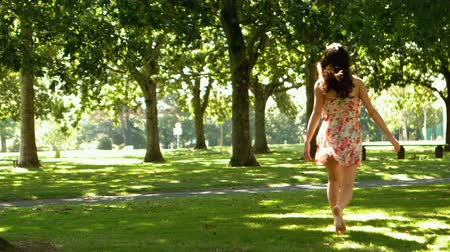 brown dress : Attractive brunette bouncing through park in slow motion