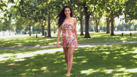 gündelik kıyafetler : Gorgeous happy brunette walking in park in slow motion