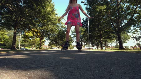 inline skating : Smiling blonde skating in park in slow motion