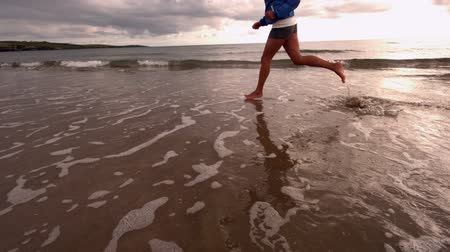 lento : Woman running at the beach in slow motion