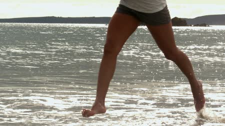 Female legs running at the beach in slow motion Vídeos