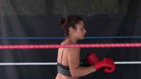 Sporty determined brunette kick boxing in boxing ring