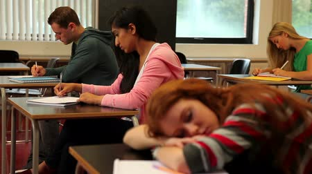 Student asleep at her desk in class in a college Vídeos
