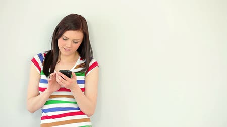 Happy young woman texting on her phone against a white wall