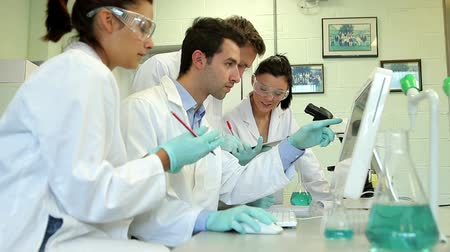 ученый : Science students working on an experiment together in college