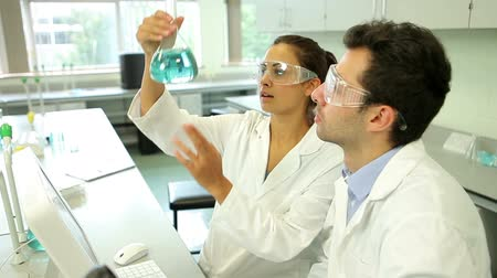 Science students looking at blue chemical together using computer at the university Vídeos