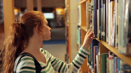 Focused student picking a book in the library in college