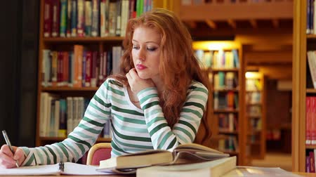 Focused student studying in the library in college Vídeos