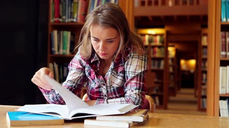 Happy student studying at desk in the library in college