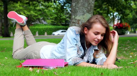 Happy student lying on the grass and answering her phone in college campus