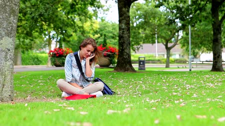 Happy student sitting on the grass making a phone call in college campus