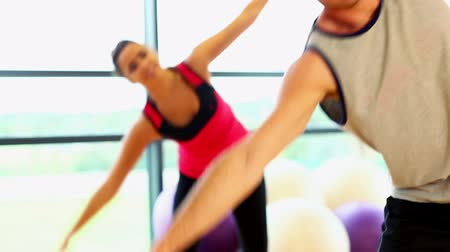 fit : Two sporty friend stretching their bodies in fitness hall