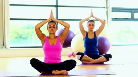 Lovely calm women meditating sitting in lotus position on exercise mats