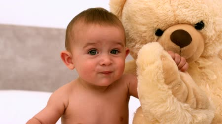 smích : Cute baby on a bed with teddy bear in slow motion