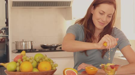 grejpfrut : Woman squeezing orange over her fruit salad in slow motion Wideo