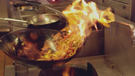 kızartma : Chef tossing flaming stir fry in slow motion