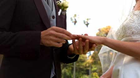 подвенечное платье : Man placing ring on brides finger in slow motion