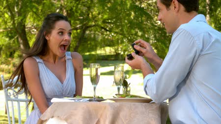 öneri : Man proposing marriage to his shocked girlfriend in slow motion Stok Video