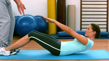 eğitici : Woman doing sit ups with her trainer in slow motion