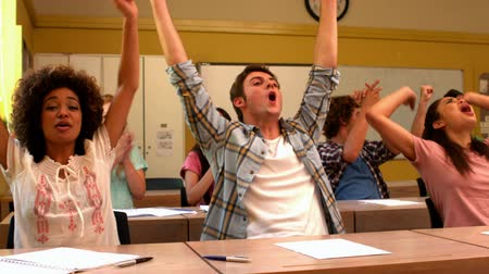 torcendo : Excited students cheering in classroom in slow motion Stock Footage