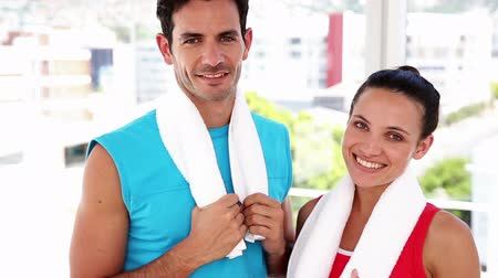 Fit couple smiling at camera at the gym