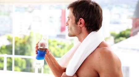 towel : Fit man drinking water from bottle at the gym
