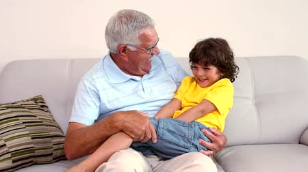 grandchild : Senior man sitting on couch with his grandson at home in the living room