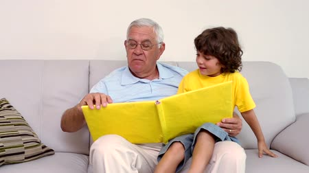 grandchild : Senior man sitting on couch with his grandson looking at photo album at home in the living room