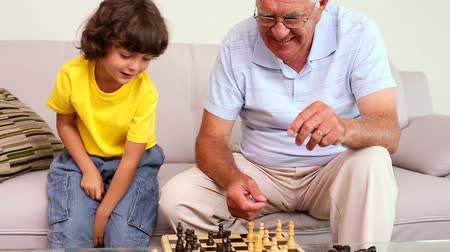 xadrez : Senior man sitting on couch with his grandson playing chess at home in the living room