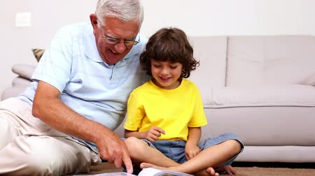 grandchild : Senior man sitting on floor with his grandson looking at photo album at home in the living room Stock Footage