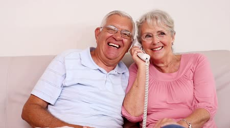 casas : Senior couple sitting on sofa talking on the phone at home in the living room