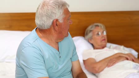 argumento : Senior couple not speaking after an argument on bed at home in the bedroom