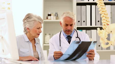 male : Doctor explaining a spine xray to patient in his office at the hospital Stock Footage